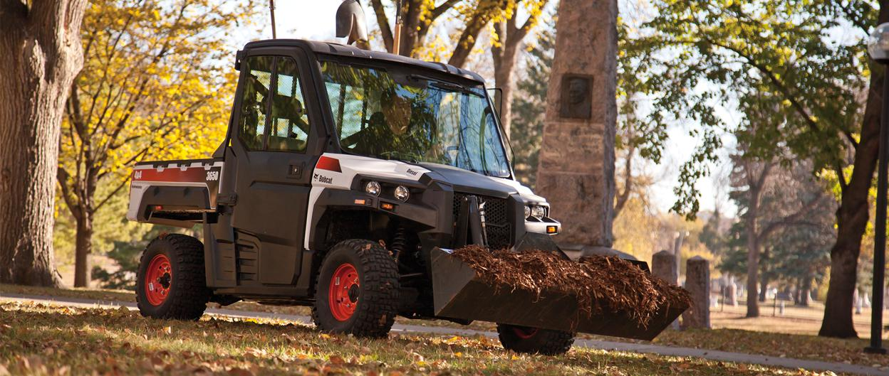 Bobcat 3650 utility vehicle with bucket attachment hauls mulch through a wooded area.
