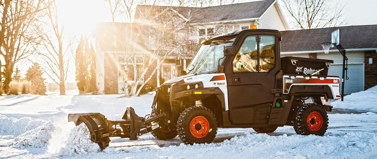Bobcat 3650 utility vehicle (UTV) with a snow V-Blade attachment clearing a residential street.