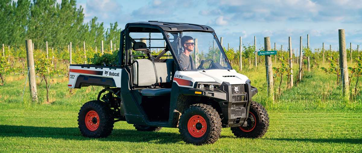 Bobcat UV34 Utility Vehicle With Cargo Box Full Of Yard Waste Traveling Through An Orchard