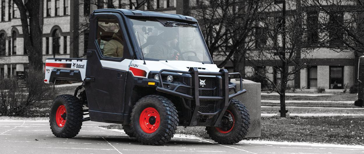 Customer Drives A Bobcat UV34 Utility Vehicle (UTV) Down The Sidewalk Of An Urban Worksite