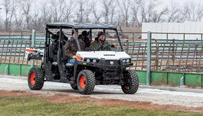 Farmer With Three Passengers Drives On Gravel Road In Bobcat UTV In Snow