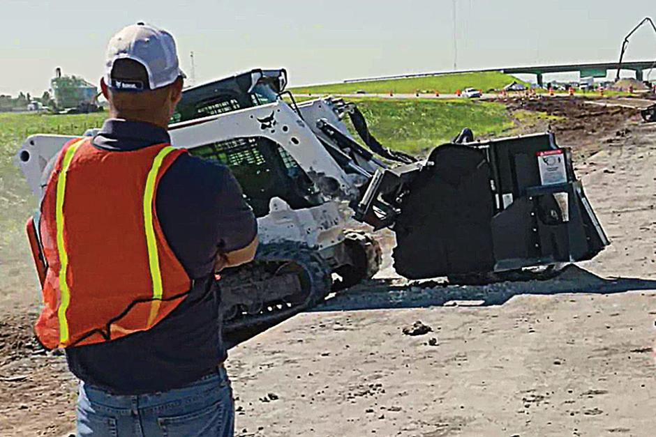 Construction Worker In Safety Vest Watching Bobcat Wheel Saw Cut Through Concrete Road