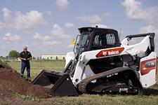 Operator Using MaxControl Remote To Direct His Bobcat Compact Track Loader With Bucket Attachment To Move Dirt